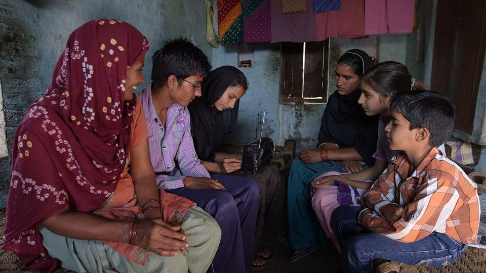 Family gathers to listen to radio, India