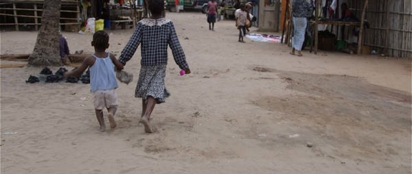 Two small children skip through the streets of Pemba, Mozambique