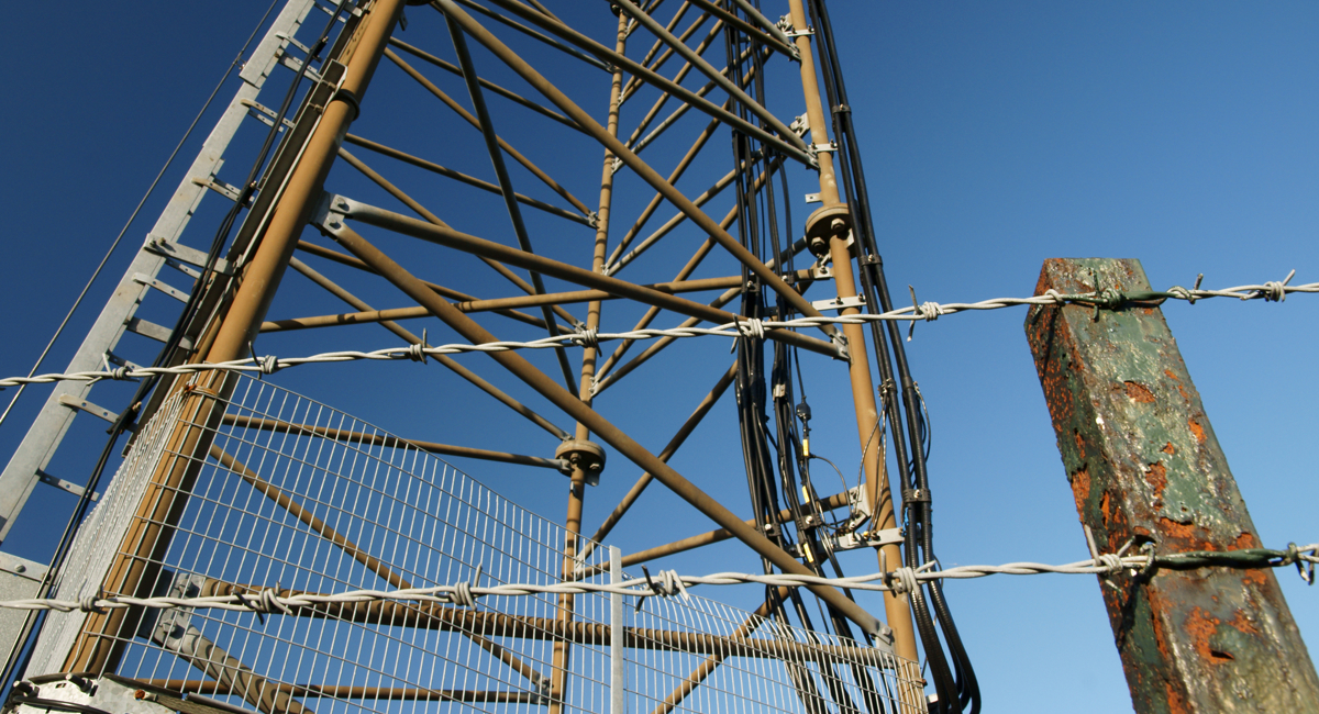 Radio mast behind a barbed wire fence