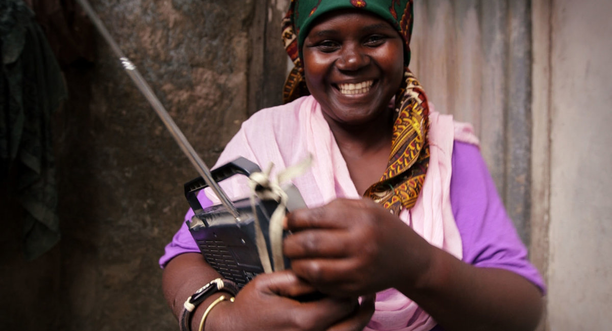 Woman smiles holding her radio, Mozambique