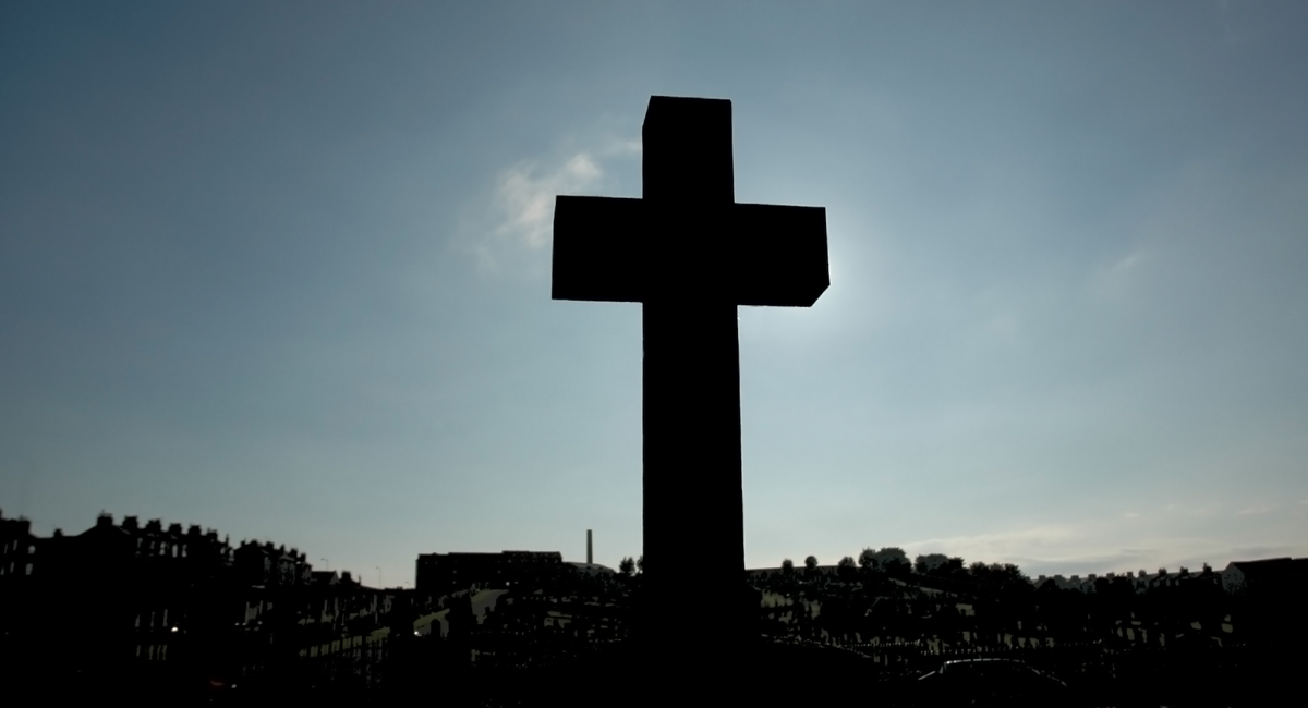 a cross silhouetted by the sun