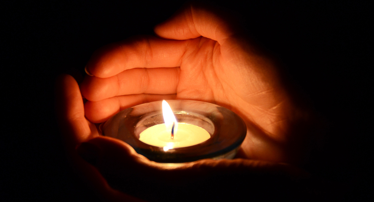 a hand shields a candle