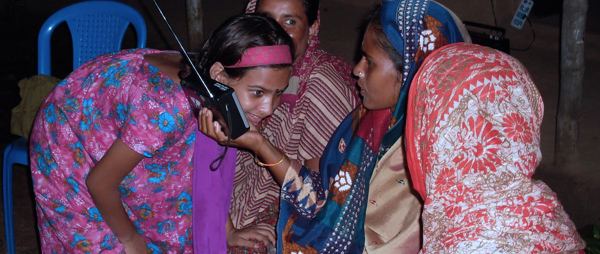 Women in Bangladesh gather around a radio