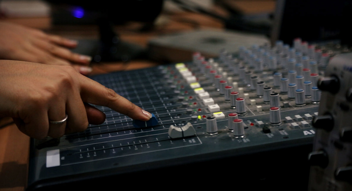 A womans hand on a mixing desk