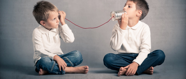Two boys use a tin can telephone with string