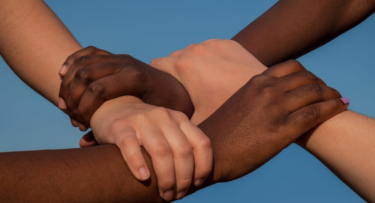 Joined hands of multiracial friends in cooperation as team