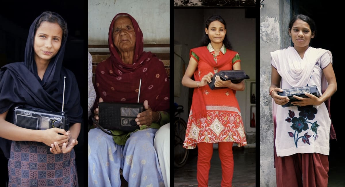 A row of female listeners with their radios stand in their doorways in India